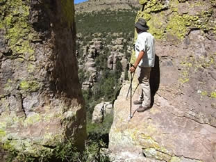 photo of a hiker standing on a ledge looking into a canyon