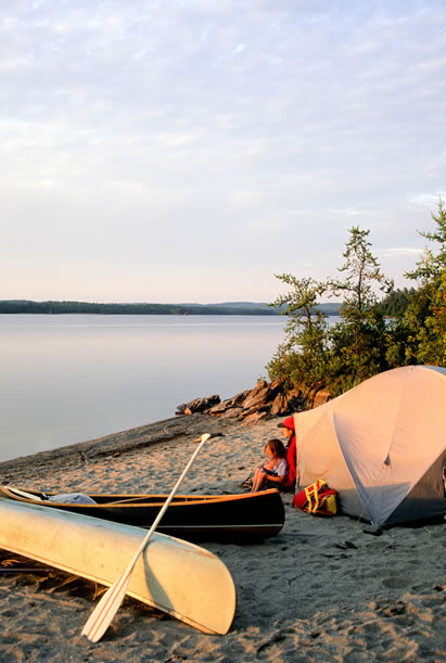 photo of a tent on a beach, canoe and family nearby