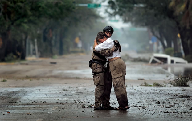 photo of people embracing, storm and flood damage evident