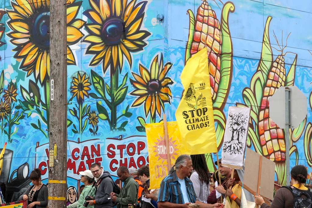 photo of demonstrators in front of a colorful mural