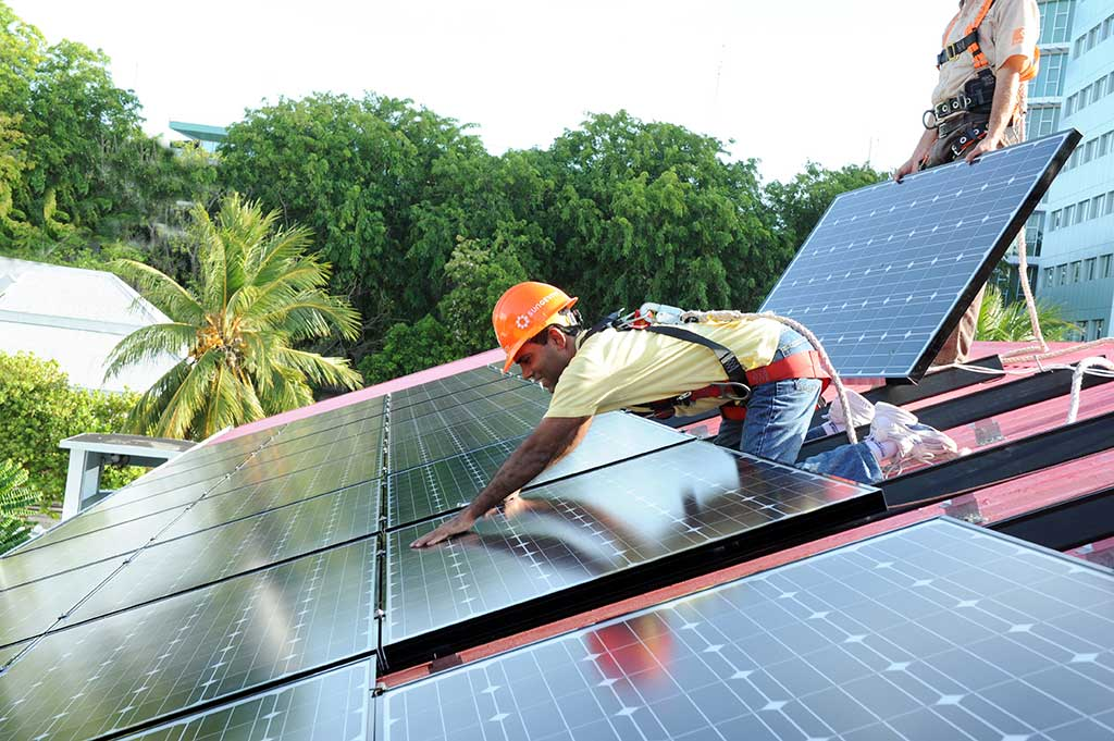photo of someone installing a solar array
