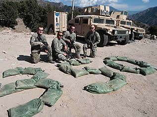 photo of men in camouflage posing near the number 350 spelled in sandbags on the ground, humvees and firearms evident