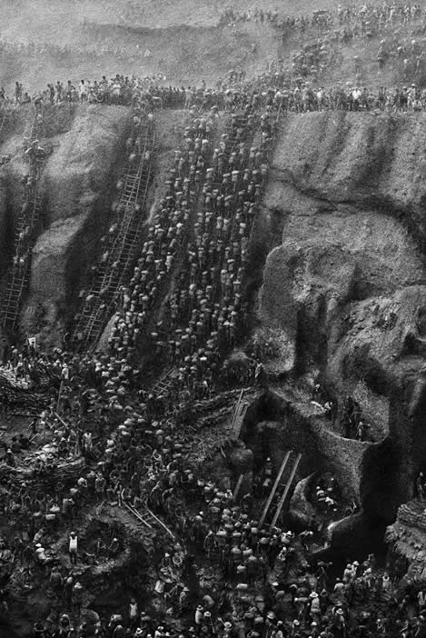 photo of hundreds of people climbing ladders into a steep mine