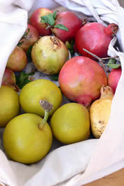 photo of pears and pomegranates in a cloth sack