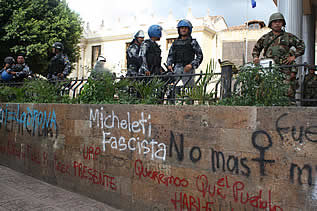 photo of soldiers standing above a wall covered with protest graffiti, including words: Micheletti Fascita