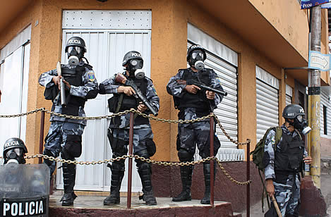 photo of three gas-mask and aromor wearing police, holding tear-gas launchers, word 'policia' on their helmets and shields