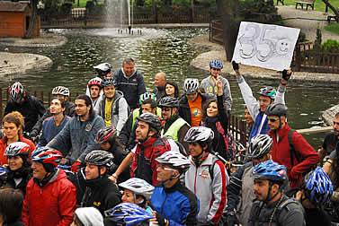 photo of bicycle-helmet wearing demonstrators by a watercourse, one holding a sign that reads: 350