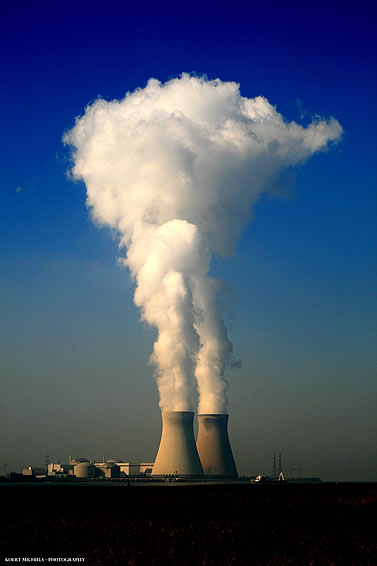 photo of a power plant, cooling towers steaming