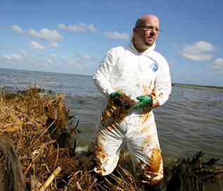 photo of a man in an oily contamination suit on the shore