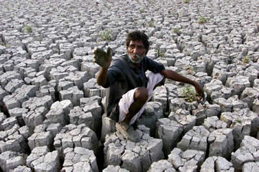 photo of a man sitting on dry, cracked mud and reaching his hand towards us