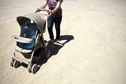 photo of a woman in a dry landscape pushing a baby stroller; in the stroller is a plastic 20 liter jug of water