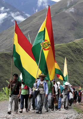 photo of people marching in a hilly landscape, carrying Bolivian flags
