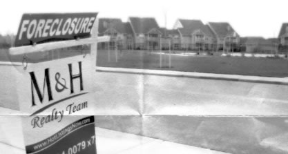 antiqued photo of a lawn for-sale sign, foreclosure prominently displayed. A housing development is in the background