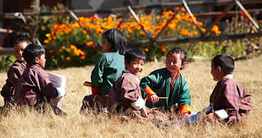 photo of smiling children sitting in a field