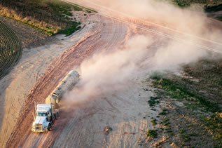 aerial photo of a tanker truck raising a large plume of dust on a rutted unpaved road