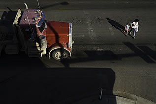 aerial photo of a woman and child crossing a street, tractor-trailer truck waiting for their progress