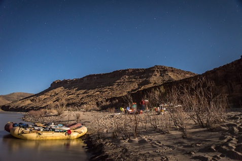 photo of a raft pulled up to an inviting sandbar on a desert river under an evening sky