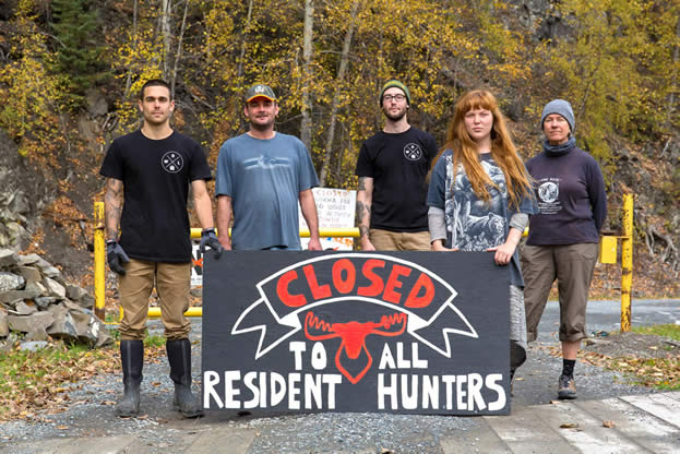 photo of a group blocking a road with a sign that reads, closed to all resident hunters