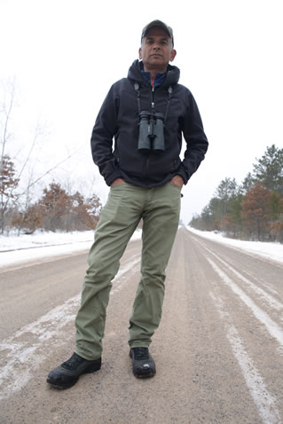 photo of a man standing in a snowy road