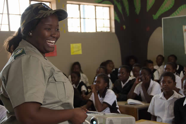 photo of a woman in a khaki uniform in front of a classroom full of children