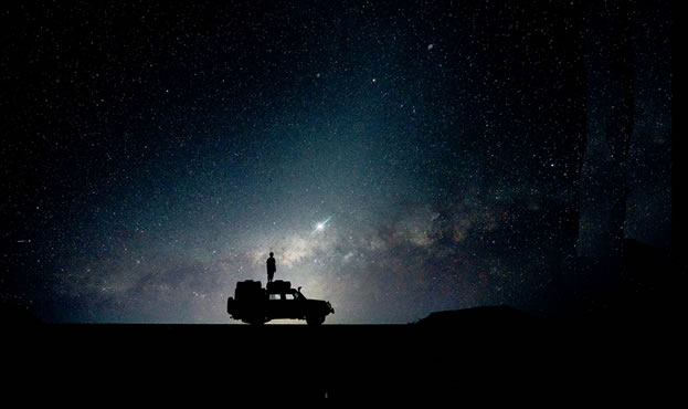 night photo, bright stars silhouette a person standing on a laden vehicle
