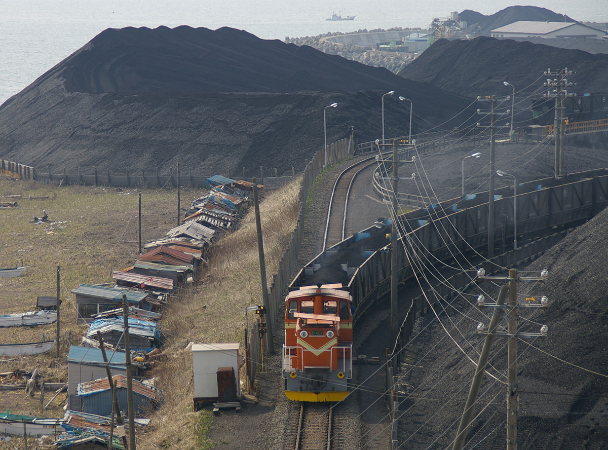 photo of a train going through coastal Japan, hill of coal in the background