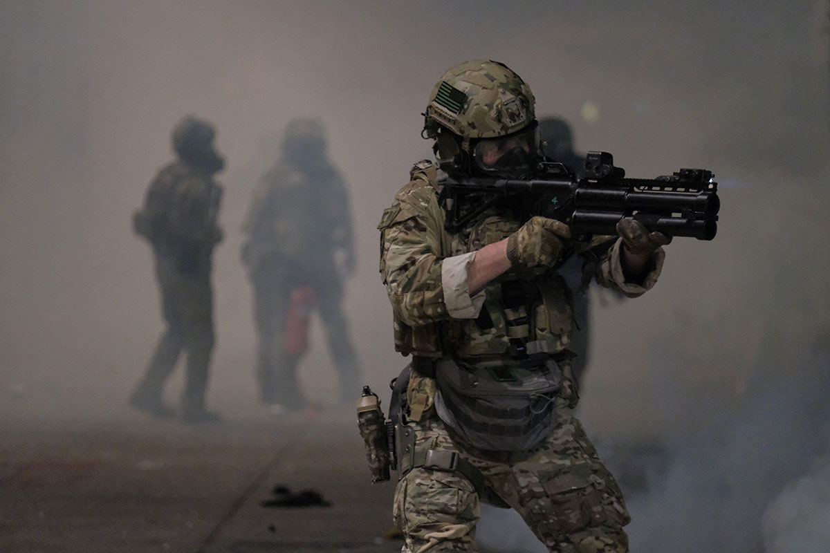 photo of a armored soldier holding a weapon in a smoky outdoor space