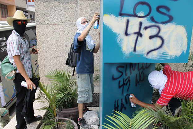 photo of people in masks spray-painting graffiti