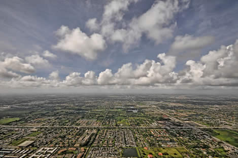 photo of a semitropical cloudy sky, and a long vista of urban habitation, sprawl