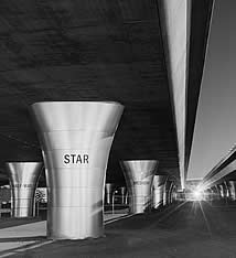 photo of a freeway overpass, pillars labeled star, half-way, medium; it is well lit at night