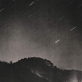 night photo of a tree covered hillside, streaks of timelapse stars above