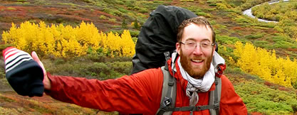 photo of a man wearing a backpack in a multicolored fall prairie landscape. He looks happy