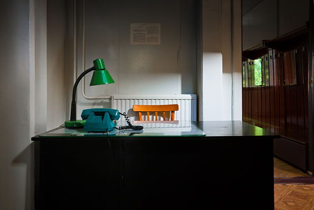 photo of a desk in a plain office, old-style telephone atop it