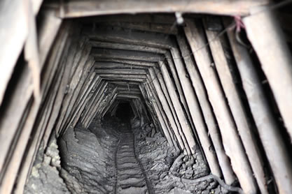 photo of a mineshaft, wooden bracing and cart tracks evident