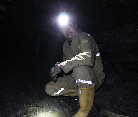 photo of a man underground, wearing a jumpsuit and hardhat with a headlamp