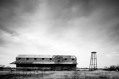 photo of a farm building in a flat arid landscape
