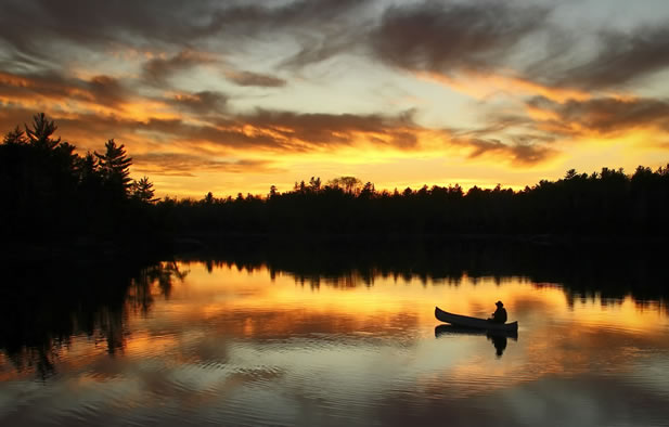 photo of a morning on a lake in the woods where someone is paddling a canoe