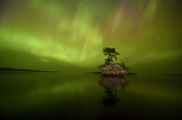 photo of a rock with an overhanging base and a single tree in the midst of a still lake, aurora in the sky behind