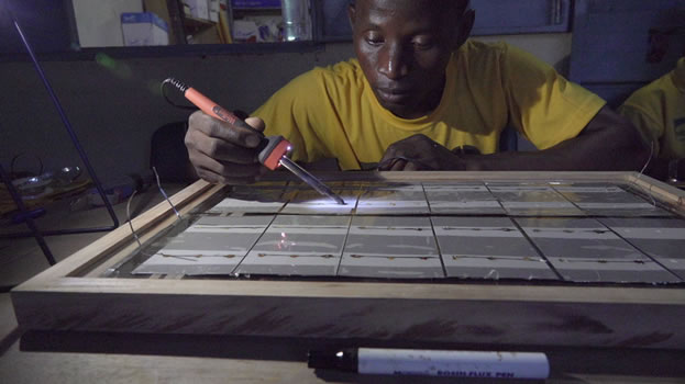 photo of a man with a soldering iron working on a solar installation