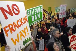photo of people in a meeting with signs that say: No Fracking Way and Statewide Ban