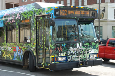 photo of a city bus, painted with vines and flowers