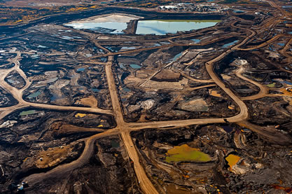 aerial photo of a mining complex, multihued ponds of waste visible