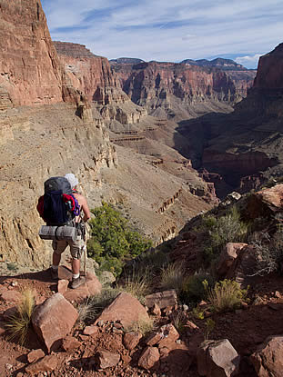 photo of a backpacker at the rim of the grand canyon
