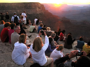 photo of a group of people on the rim of the canyon at sunset