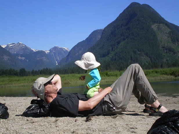 photo of a man holding his small child and relaxing in the mountains