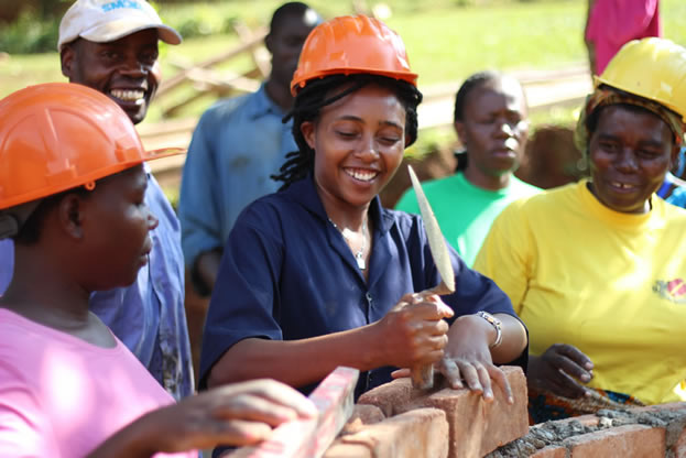 photo of women wearing hard-hats and bricklaying, they seem amused