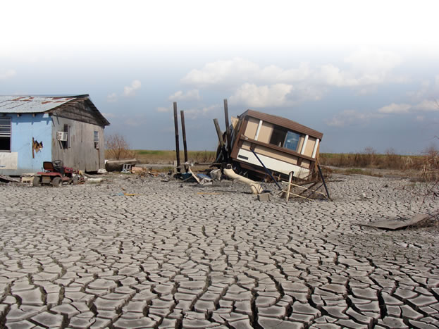 photo of a ruined home, on broken stilts, over a floodplain
