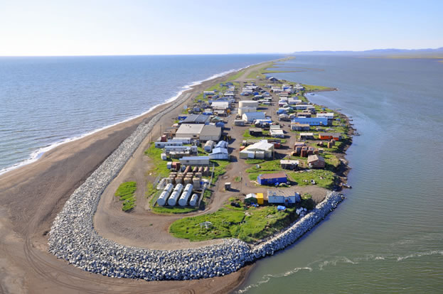 photo of a village on a sand-spit in the sea, riprap seawalls at one end