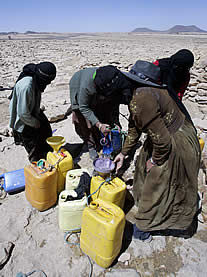 photo of women at a well in arid land