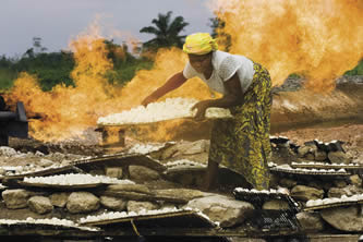 photo of a woman working near fire in a tropic setting